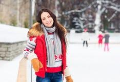 Junges und hübsches Mädchen, das auf eine Eisbahn im Freien eisläuft Stockbild