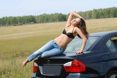 Junges und reizvolles Mädchen auf einem Auto Stockfotografie