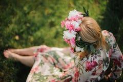 Junges und schönes Mädchen in einem Blumendiadem, das auf dem Gras sitzt Lizenzfreies Stockbild