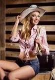 Junges und sexy Cowgirl, das in einer Scheune aufwirft Stockbilder
