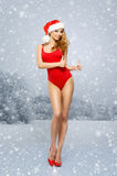 Junges und sexy Sankt-Mädchen in einem roten Badeanzug auf einem schneebedeckten Hintergrund Stockfotos