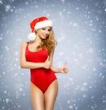 Junges und sexy Sankt-Mädchen im roten Badeanzug mit einem Weihnachten Lizenzfreies Stockbild