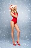 Junges und sexy Sankt-Mädchen in einem roten Weihnachtsbadeanzug Stockfoto