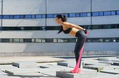 Junges und sportliches Mädchentraining mit dem elastischen Band im Freien Lizenzfreies Stockfoto