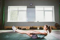 Junges und starkes Mädchen mit einem Lächeln, das Übungen für die Muskeln des Magens, Presse auf dem Boden in der Spore tut Stockfoto