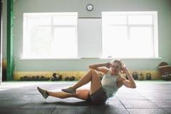 Junges und starkes Mädchen mit einem Lächeln, das Übungen für die Muskeln des Magens, Presse auf dem Boden in der Spore tut Stockbild