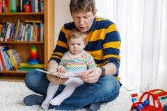 Junges Vaterlesebuch mit seinem netten entzückenden Babytochtermädchen Lächelndes schönes Kind und Mann, die zusammen herein sitz lizenzfreies stockbild