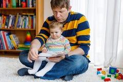 Junges Vaterlesebuch mit seinem netten entz?ckenden Babytochterm?dchen stockfotos