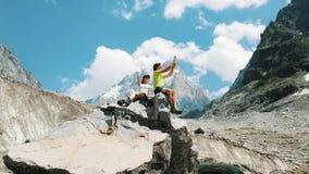 Junges verheiratetes Paar von Touristen sitzen auf einem Felsen und werden fotografiert und selfie auf einem Smartphone in einer  stockbilder