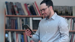 Junges Video-Conferencing des männlichen Lehrers auf Tablette an der Bibliothek stock footage