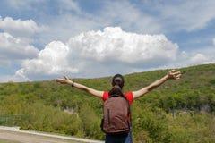 Junges Wanderermädchen mit Rucksack genießend und zum Himmel mit Wolken schauend Stockbild