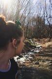 Junges weißes Mädchen, das im Wald und in einem Stromfließen wandert lizenzfreie stockfotos