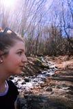 Junges weißes Mädchen, das im Wald und in einem Stromfließen wandert stockbilder