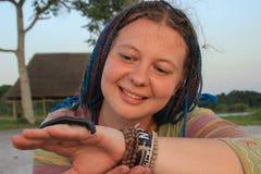 Junges weißes Mädchen der Reisende mit dem Haar in den blauen Zöpfen hält an Hand einen Wurm Julida lizenzfreie stockfotos