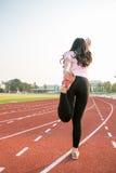 Junges weibliches Aufwärmen auf einem laufenden trac Stockfoto