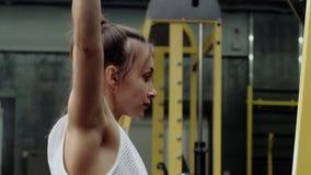 Junges weibliches Eignungsmodell, das mit Gewichten f?r die Arme und die R?ckenmuskulatur ?bt stock video footage