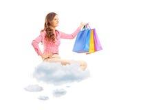 Junges weibliches Fliegen auf Wolken und Holdingeinkaufstaschen Stockfotos