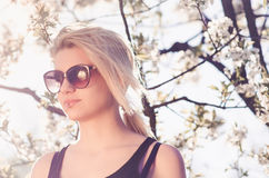 Junges weibliches Frühlingsporträt mit Sonnenbrille Stockfotos