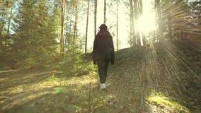 Junges weibliches Gehen unter Bäumen im Wald stock video