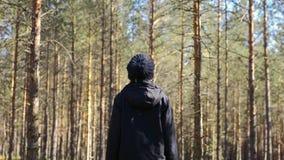 Junges weibliches Gehen unter Bäumen im Wald stock video footage