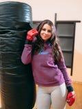 Junges weibliches kickboxer, das nahe Sandsack aufwirft stockbild