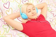 Junges weibliches Lügen auf einem Bett und einer hörenden Musik Stockbilder