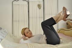 Junges weibliches Modell, das auf Bett 04 liegt Stockfotografie