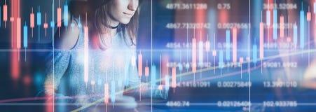 Junges weibliches Modell, das im Nachtmodernen Büro arbeitet Technisches Preisdiagramm und Indikator-, Rotes und Gr?neskerzenst?n stockbild