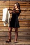 Junges weibliches Modell, das weiße Jacke auf Fotoschießen überprüft Stockbild