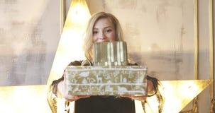 Junges weibliches Modell, das Weihnachtsgeschenkboxen lächelt und gibt stock video