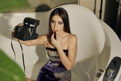 Junges weibliches Modell mit dem langen brunette Haar, das am Bad aufwirft, malt Lippen mit Lippenstift und Handeln selfie auf de lizenzfreies stockbild