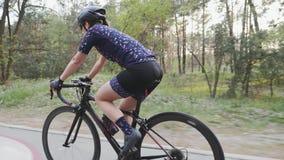 Junges weibliches Radfahrerreitfahrrad im Park als Teil ihres Ausbildungsprogramms Seite folgen Schuss stock footage