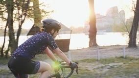 Junges weibliches Reitenfahrrad mit Fluss, Stadt und Sonnenuntergang auf dem Hintergrund Radfahrenkonzept Langsame Bewegung