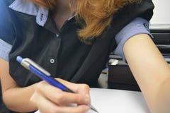 Junges weibliches Schreiben auf Papier stockbild