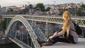 Junges weibliches Sitzen auf der Spitzenaussichtsplattform auf dem Duero-Fluss, die Brücke Dom Luis übersehend I, Porto Stockbild