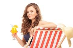 Junges weibliches Sitzen auf einem Sonnenruhesessel und Trinken eines Cocktails Lizenzfreies Stockfoto