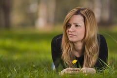 Junges weibliches Sitzen auf Gras Stockfotos