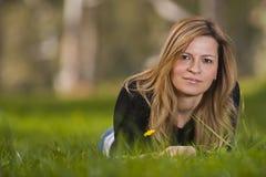 Junges weibliches Sitzen auf Gras Stockfoto