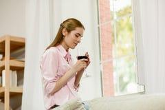 Junges weibliches Sitzen nahe bei dem Fenster, denkend, Weinglas mit beiden Händen halten lizenzfreie stockfotografie