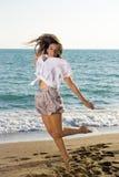 Junges weibliches Springen am strandnahen Lizenzfreie Stockfotografie