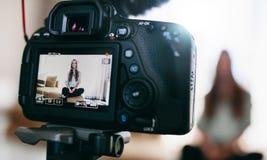 Junges weibliches vlogger auf Kameraschirm Lizenzfreie Stockfotografie