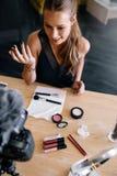 Junges weibliches vlogger, das ein Make-upvideo für ihr vlog notiert Stockfoto