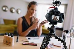 Junges weibliches vlogger, das ein Make-upvideo für ihr vlog notiert Lizenzfreie Stockbilder