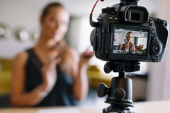 Junges weibliches vlogger, das ein Make-upvideo für ihr vlog notiert Stockbilder