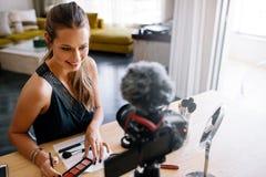 Junges weibliches vlogger, das ein Make-upvideo für ihr vlog notiert Stockfotografie