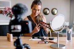 Junges weibliches vlogger, das eine Make-upsendung für ihr vlog notiert Lizenzfreies Stockfoto