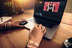 Junges weibliches vlogger, das ihr vlog auf Computer redigiert Lizenzfreie Stockfotos