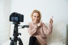 Junges weibliches vlogger nahe bei Kamera zu Hause Aufnahmevideo für Blog Stockfotografie