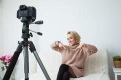 Junges weibliches vlogger nahe bei Kamera zu Hause Aufnahmevideo für Blog Lizenzfreie Stockfotos