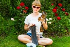 Junges wooman mit Näharbeit und Hund Stockfotografie